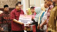 Menteri Koperasi dan UKM Puspayoga secara simbolis memberikan bantuan pemerintah melalui program Wirausaha Pemula saat sinergi program pembiayaan Kementerian Koperasi dan UMK dengan pemerintah daerah Provinsi NTB, Jumat (12/5). (Liputan6.com/Angga Yuniar)