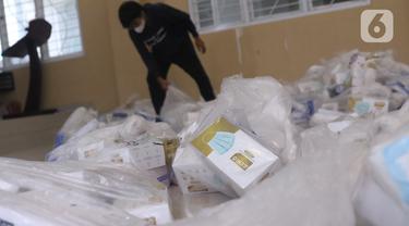 Kesibukan pendistribusian alat pelindung diri (APD) untuk setiap TPS di Parigi, Tangerang Selatan, Selasa (8/12/2020). Panitia Pemungutan Suara (PPS) menyiapkan APD seperti masker, sarung tangan, baju hazmat, ember pencuci tangan untuk keperluan Pilkada Tangsel. (Liputan6.com/Angga Yuniar)