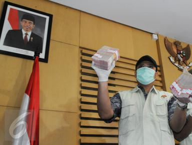 Petugas menunjukkan barang bukti hasil OTT terkait dugaan suap pengurusan perkara Saipul Jamil di KPK, Jakarta, Kamis (16/6). Kakak Saipul Jamil diketahui melakukan suap kepada Panitera PN Jakarta Utara dengan uang Rp 250 juta. (Liputan6.com/Helmi Afandi)