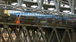 Anak-anak Ciliwung tampak riang saat melompat ke aliran sungai Ciliwung dari atas jembatan Kalibata, Jakarta, Jumat (13/11). Meningginya air sungai Ciliwung dimanfaatkan anak-anak Ciliwung untuk berenang dan bermain air. (Liputan6.com/Yoppy Renato)