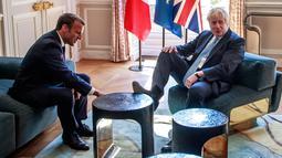 PM Inggris, Boris Johnson menaruh kaki di atas meja di depan Presiden Prancis Emmanuel Macron dalam kunjungan kenegaraan di Istana Elysee, Paris, Kamis (22/8/2019). Awak media mengabadikan momen ketika Johnson menumpangkan kakinya di meja kopi. (Christophe Petit Tesson, Pool via AP)