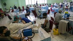 Suasana proses vaksinasi COVID-19 terhadap pedagang di Pasar Induk Kramat Jati, Jakarta Timur, Selasa (9/3/2021). Penyuntikan vaksin tahap pertama ini menargetkan 1.000 peserta. (Liputan6.com/Faizal Fanani)