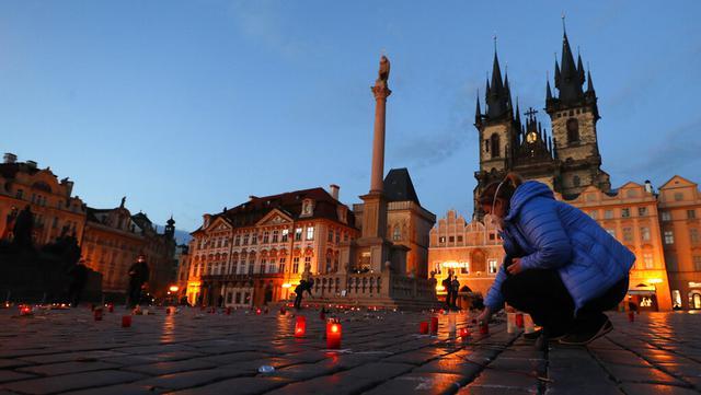Seorang wanita menyalakan lilin untuk memberi penghormatan kepada para korban pandemi COVID-19 di Alun-Alun Kota Tua, Praha, Republik Ceko, Senin (29/3/2021). Pandemi COVID-19 menimbulkan penderitaan yang luar biasa di seluruh Eropa tengah, termasuk Republik Ceko. (AP Photo/Petr David Josek)