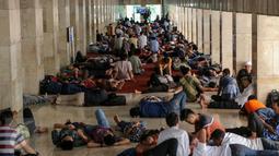 Umat muslim bersantai di koridor Masjid Istiqlal, Jakarta, Jumat (19/6). Selain membaca Alquran, sejak memasuki bulan Ramadan, warga setiap hari memenuhi Masjid Istiqlal untuk beristrahat sambil menunggu waktu berbuka puasa. (Liputan6.com/Faizal Fanani)