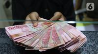 Teller menunjukkan uang rupiah di money changer, Jakarta, Rabu (9/9/2020). US$ 1 dibanderol Rp 14.780/US$ di pasar spot. Rupiah melemah 0,14% dibandingkan dengan penutupan perdagangan kemarin. (Liputan6.com/Angga Yuniar)