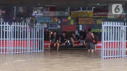 Sejumlah orang beristirahat saat banjir merendam sejumlah pertokoan di Kawasan Bendungan Hilir (Benhil), Jakarta Pusat,  Selasa (25/2/2020). Salah satu wilayah terdampak banjir yakni kawasan Benhil hingga membuat akses jalan untuk sementara terputus.  (Liputan6.com/Angga Yuniar)