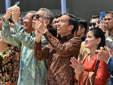 Presiden RI Joko Widodo didampingi Ibu Negara Iriana dan PM Singapura Lee Hsien Loong dan istrinya Ho Ching menyaksikan manuver F16 Angkatan Udara Singapura dan F16 TNI-AU di Marina Bay Cruise Center di Singapura, Kamis (7/9). (AFP Photo/Roslan Rahman)