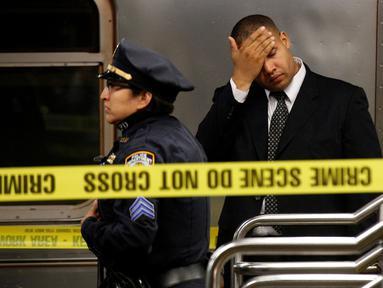 Petugas NYPD melakukan penyelidikan di lokasi tewasnya seorang perempuan di stasiun Time Square, New York, Senin (7/11). Perempuan malang itu tewas setelah didorong ke jalur subway ketika kereta nomor 1 sedang memasuki stasiun. (REUTERS/Brendan McDermid)