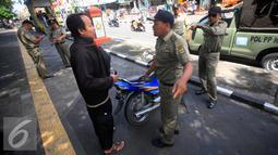 Petugas Satpol PP berdiskusi dengan seorang yang terkena razia yang parkir di kawasan pendestrian Malioboro, (19/4). Petugas memberikan surat peringatan dan mengambil kartu identitasnya yang di tahan di KUPT Malioboro. (Liputan6.com/Boy Harjanto)