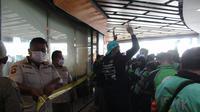 Satpol PP Kota Depok menyegel McD Ciplaz Depok dikarenakan melanggar PPKM Kota Depok. (Liputan6.com/Dicky Agung Prihanto)