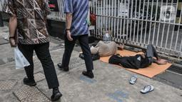 Pekerja melintasi pencari suaka yang tidur di depan Kantor UNHCR Kebon Sirih, Jakarta, Kamis (1/4/2021). Imigran yang terdiri atas orang dewasa hingga anak-anak ini tidur di pinggir jalan menuntut agar proses perpindahan mereka ke negara negara tujuan segera dipercepat. (merdeka.com/Iqbal S Nugroho
