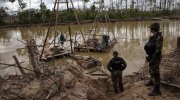 Polisi berdiri dekat mesin penambangan ilegal saat melaksanakan Operation Mercury di Provinsi Tambopata Peru, 1 April 2019. Pemerintah Peru mengerahkan polisi dan tentara untuk mengusir ribuan penambang ilegal yang menebangi hutan Amazon untuk mencari emas. (AP Photo/Rodrigo Abd)