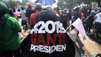 Massa menggunakan kaus bertulisakan #2019GantiPresiden saat deklarasi akbar di Monas, Jakarta, Minggu (6/5). Acara ini juga diramaikan dengan penjualan kaus dan atribut bertagline #2019GantiPresiden. (Merdeka.com/Iqbal Nugroho)