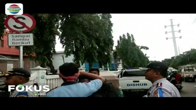 Petugas beri hukuman hormat tiang rambu lalu lintas kepada pemilik kendaraan yang parkir sembarangan di kawasan Jakarta Timur.