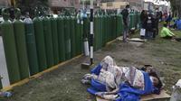 Sejumlah orang beristirahat di samping tangki oksigen kosong saat menunggu toko isi ulang buka di Callao, Peru, Senin (25/1/2021). Di tengah pandemi COVID-19, beberapa orang mengatakan mereka telah antre sehari sebelumnya untuk menjadi yang pertama saat toko buka. (AP Photo/Martin Mejia)