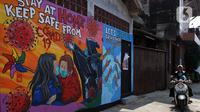 Pemotor melintas di depan mural bertema virus corona COVID-19 yang menghiasi dinding rumah di kawasan Pangkalan Jati Baru, Depok, Jawa Barat, Selasa (2/6/2020). Mural bertulis 'Stay At Home, Keep Safe From COVID-19' itu untuk mengingatkan warga akan bahaya COVID-19. (Liputan6.com/Johan Tallo)