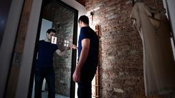 Wesley Bliss menunjukkan cara berinteraksi dengan cermin pintar Oak Fitting Room di sebuah butik, New York, AS (7/2). Cermin ini juga dapat mengukur tubuh sehingga merekomendasikan pakaian yang cocok. (AFP Photo / Jewel Samad)