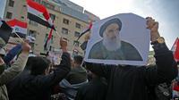 Rakyat Irak membawa foto ulama Syiah top negara itu, Ayatollah Ali al-Sistani, ketika mereka berdemonstrasi di ibu kota Tahrir Square, Baghdad, 5 Desember 2019. (Foto: AFP)