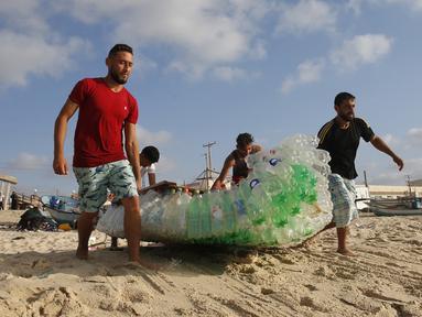 Nelayan Palestina, Mouad Abu Zeid (kanan) dan teman-temannya membawa perahu yang terbuat dari botol plastik bekas di sebuah pantai di Rafah, Jalur Gaza, 14 Agustus 2018. Zeid menggunakan 700 botol plastik bekas menjadi sebuah perahu. (AFP/SAID KHATIB)