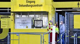 Petugas Kesehatan dengan menggunakan masker berjaga di depan Stadion Signal Iduna Park, Jerman, Sabtu (4/4/2020). Stadion Borussia Dortmund ini dialihfungsikan menjadi tempat pusat pengujian COVID-19. (AP/Martin Meissner)