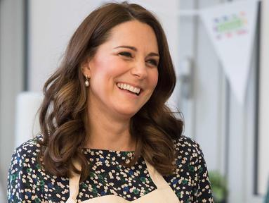 Kate Middleton tersenyum saat memasak dalam persiapan acara Commonwealth Big Lunch di Luke's Community Centre, London, Inggris (22/3). Big Lunch merupakan acara tahunan terbesar di Inggris. (Paul Edwards/ Pool via AP)