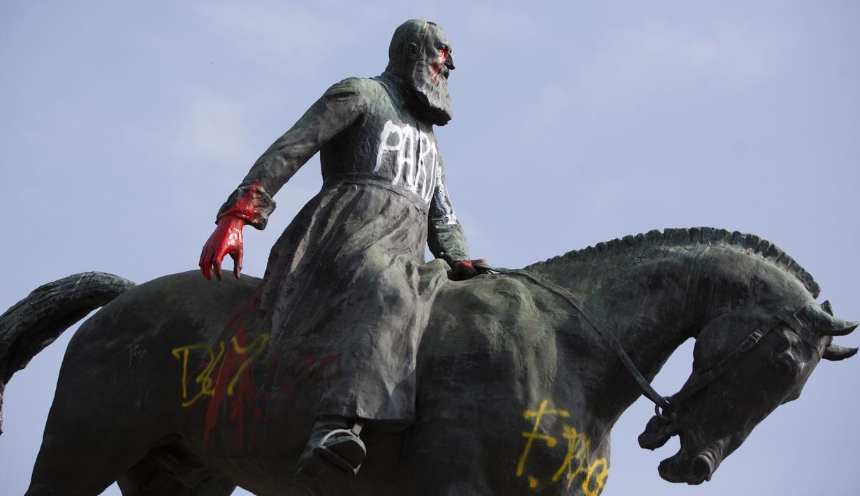 Patung Raja Belgia Leopold II dicoret dengan cat dan grafiti di Brussel, Belgia, Rabu (10/6/2020). Di tengah protes dunia atas kematian George Floyd, patung Raja Leopold II dirusak karena pemerintahannya yang brutal ketika menguasai Kongo ratusan tahun silam. (AP Photo/Virginia Mayo)
