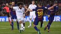 Bek Real Madrid, Marcelo, berusaha melewati bek Barcelona, Jordi Alba, pada laga La Liga Spanyol di Stadion Camp Nou, Barcelona, Minggu (6/5/2018). Kedua klub bermain imbang 2-2. (AFP/Josep Lago)
