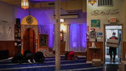 Sukarelawan membawa bahan makanan untuk yang membutuhkan saat anggota Muslim Giving Back lainnya beribadah di Pusat Komunitas Muslim di lingkungan Bay Ridge, Brooklyn, New York, pada 27 April 2020. Kegiatan komunitas Muslim tersebut berlangsung selama Ramadan. (AP Photo/Wong Maye-E)