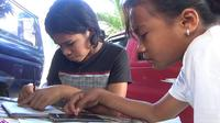 Foto: Novita Temi (baju hitam) bersama temannya, Oliv Paskela, sedang belajar daring  (Liputan6.com/Dion)