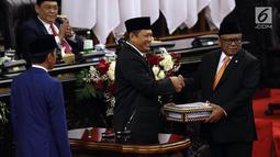 Ketua DPR Bambang Soesatyo (tengah) menyerahkan RUU tentang APBN TA 2020 beserta Nota Keuangan dan pendukungnya kepada Ketua DPD Oesman Sapta Odang dalam Sidang Paripurna di Gedung DPR, Jakarta, Jumat (16/8/2019). DPR akan membahas RAPBN 2020 untuk disahkan menjadi UU. (Liputan6.com/JohanTallo)