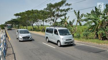 Sejumlah kendaraan melintas di Jalur Pantura, Jawa Barat, Minggu (2/6/2019). Lalu lintas terpantau ramai lancar kendati berlakunya sistem satu arah di Jalan Tol Trans Jawa membuat kendaraan menuju Jakarta dialihkan melalui jalur arteri Pantura. (Liputan6.com/Herman Zakharia)