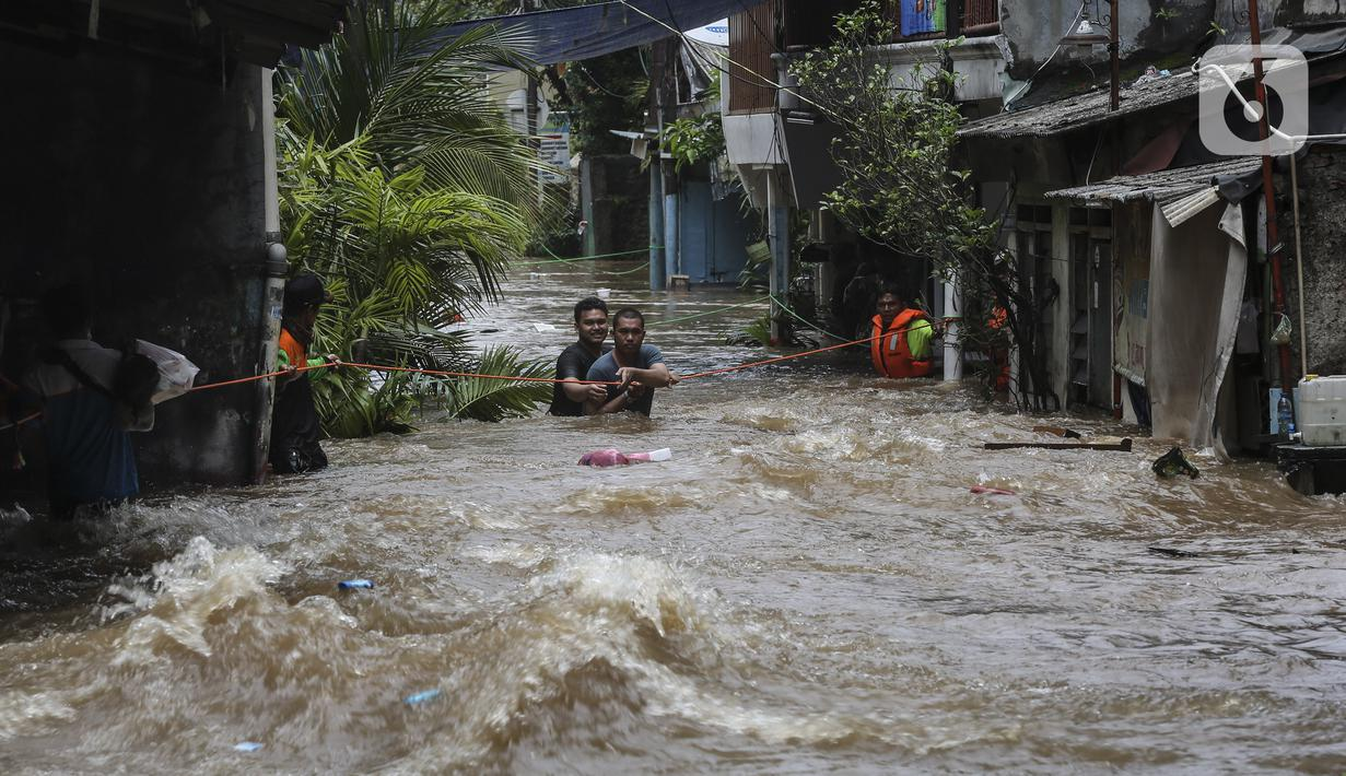 Warga berpegangan pada tali saat dievakuasi dari banjir di kawasan Tendean Jakarta, Sabtu (20/2/2021). Curah hujan yang tinggi menyebabkan banjir setinggi orang dewasa di kawasan Tendean. (Liputan6.com/Johan Tallo)