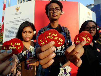 Aktivis dari Komisi Untuk Orang Hilang dan Korban Tindak Kekerasan (Kontras) menunjukan stiker saat melakukan aksi damai dengan memberikan bunga kepada warga di kawasan MH. Thamrin, Jakarta, Rabu (30/08). (Liputan6.com/Johan Tallo)
