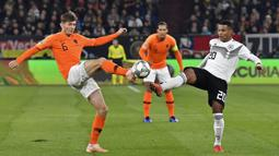 Pemain Belanda, Marten de Roon, berebut bola dengan pemain Jerman, Serge Gnabry, pada laga UEFA Nations League di Veltins Arena, Gelsenkirchen, Senin (19/11/2018). Kedua tim bermain imbang 2-2. (AP/Martin Meissner)