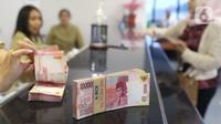Pegawai tengah menghitung mata uang rupiah di penukaran uang di Jakarta, Rabu (4/3/2020). Rupiah ditutup menguat 170 poin atau 1,19 persen menjadi Rp14.113 per dolar AS dibandingkan posisi hari sebelumnya Rp14.283 per dolar AS. (Liputan6.com/Angga Yuniar)