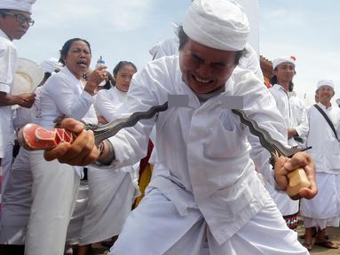 Seorang pria menusukkan keris ke tubuhnya saat menggelar ritual Melasti di Bali, Senin (4/3). Ritual Melasti ini dirayakan menjelang Nyepi 2019. (AP Photo/Firdia Lisnawati)