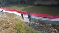 Pegiat lingkungan di Kota Bogor membentangkan bendera sepanjang 33 meter di aliran Sungai Ciliwung.(Foto:Liputan6/chmad Sudarno)