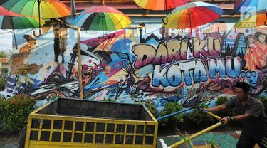 Warga melintasi gambar mural/grafiti di Kampung Bekelir, Jalan Perintis Kemerdekaan, Kota Tangerang, Banten, Selasa (17/4). Kampung Bekelir pada 10 tahun lalu merupakan kawasan yang kumuh. (Merdeka.com/Arie Basuki)