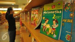 Pegawai merapihkan buku pelajaran di sebuah toko buku di Jakarta, (12/7). Menjelang dimulainya tahun ajaran baru 2016/2017 penjualan buku materi pelajaran dan buku tulis di toko buku mengalami peningkatan sekitar 50 persen. (Liputan6.com/Gempur M Surya)