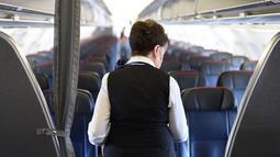 Pramugari Bette Nash memeriksa kursi penumpang sebelum melakukan penerbangan ke Boston di Bandara Ronald Reagan Washington di Arlington, Virginia (19/21). Bette Nash adalah pramugari tertua  yang kini berusia 81 tahun. (AFP Photo/Eric Baradat)