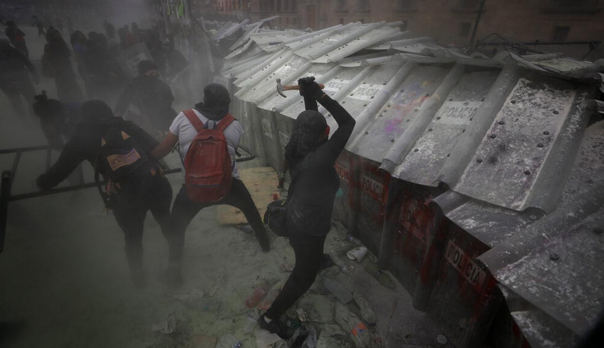 Demonstran menyerang barikade yang melindungi Istana Nasional selama pawai untuk memperingati Hari Perempuan Internasional dan memprotes kekerasan gender di Mexico City, Meksiko, Senin (8/3/2021). Hari Perempuan Internasional diperingati setiap tanggal 8 Maret. (AP Photo/Rebecca Blackwell)