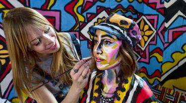 Seniman Alexa Meade (kiri) melukis wajah model Justine Jaime dalam instalasi seni 3D interaktif di Union Station, Los Angeles, Kamis (7/6). Acara ini digelar sebagai hiburan musim panas. (AP Photo/Richard Vogel)