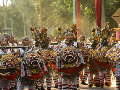 Peserta mengenakan pakaian Tari Barong pada karnaval Budaya Bali di kawasan Nusa Dua, Bali, Jumat (12/10). Karnaval tersebut untuk memeriahkan perhelatan Pertemuan Tahunan IMF - World Bank Group 2018 di Bali. (Liputan6.com/Angga Yuniar)