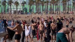 Petugas polisi meminta orang-orang untuk tidak duduk sambil berpatroli di pantai di Barcelona, Spanyol, Rabu, (20/5/2020). Berjemur dan berenang masih tidak diizinkan di pantai tersebut. (AP Photo/Emilio Morenatti)