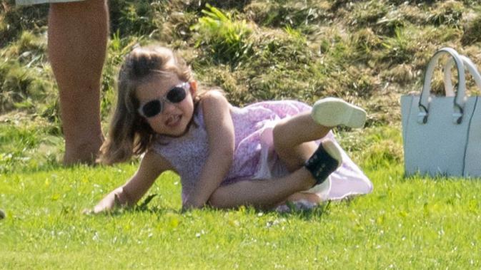 Tingkah menggemaskan Putri Charlotte saat menghadiri acara amal bertajuk Maserati Royal Charity Polo Trophy di Beaufort Polo Club, Gloucestershire, Minggu (10/6). Charlotte terlihat sangat menikmati banget aktivitas main di luar. (AP Photo)