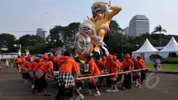 Sejumlah pemuda mengarak boneka raksasa dalam pawai Ogoh-ogoh di kawasan Monas, Jakarta, Jumat (20/3/2015). Pawai tersebut merupakan rangkaian dari prosesi menjelang Hari Raya Nyepi Tahun Saka 1937. (Liputan6.com/Johan Tallo)