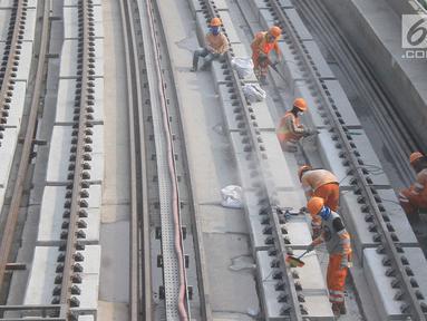 Pekerja menyelesaikan Rel Light Rail Transit (LRT) di Jakarta, Selasa (26/2). Light Rail Transit (LRT) Jabobek trase Cawang–Cibubur bakal diujicoba pada pertengahan tahun ini. (Liputan6.com/Herman Zakharia)