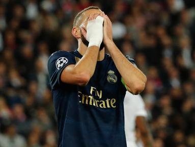 Penyerang Real Madrid, Karim Benzema menutup wajahnya dengan tangan setelah kehilangan peluang mencetak gol ke gawang Paris Saint-Germain (PSG) pada laga Grup A Liga Champions di Parc des Princes, Rabu (18/9/2019). Real Madrid kalah telak dengan skor 0-3. (AP Photo/Francois Mori)