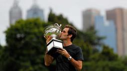 Petenis Swiss, Roger Federer mencium piala Challenge Norman Brookes di Government House, Melbourne, Australia (29/1). Federer mengalahkan petenis Kroasia Marin Cilic 6-2, 6-7(5), 6-3, 3-6, 6-1. (AP Photo/Ng Han Guan)