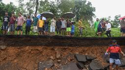Sejumlah warga berada di lokasi runtuhnya tembok di Mumbai, India (2/7/2019). Sedikitnya 15 orang tewas dan 69 orang lainya luka ketika sebuah tembok runtuh saat hujan lebat monsun. (AFP Photo/Punit Paranjpe)